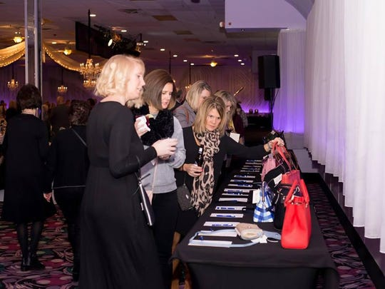 Guests browse silent auction purses at the 2018 Handbags for Hope.