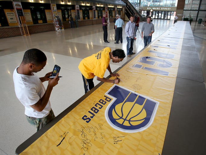 Derek Harris, left, takes a photo of his friend Gene Cox as he signs a banner wishing Indiana Pacers forward Paul George a speedy recovery inside Bankers Life Fieldhouse, on Tuesday, Aug. 5, 2014, in Indianapolis.