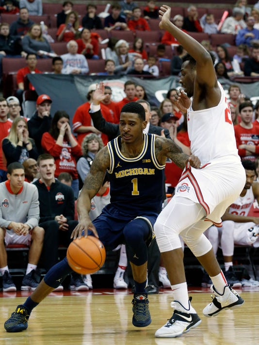 Michigan's Charles Matthews, left, drives the baseline against Ohio State's Andre Wesson during the first half of an NCAA college basketball game Monday, Dec. 4, 2017, in Columbus, Ohio. (AP Photo/Jay LaPrete)