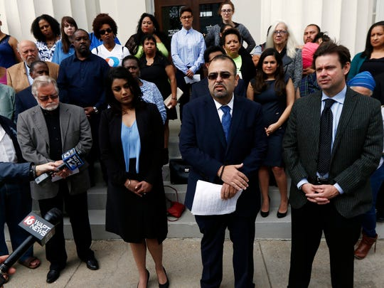 Attorney Ramiro Orozco, center, flanked by fellow immigration law attorneys Nathan Elmore, right, and Navketan Desai, third from right, speaks at a news conference Wednesday, March 1, 2017, about efforts to have Latino and Indian community members develop a forum for law enforcement and municipality leaders to help educate and explain the impact anti-immigration bills will have on their communities, in Jackson, Miss. (AP Photo/Rogelio V. Solis)