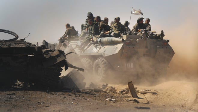 Pro-Russian rebels pass by destroyed Ukrainian military vehicles near the village of Novokaterynivka, eastern Ukraine, on Tuesday.