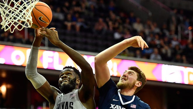 Georgetown Hoyas center Jessie Govan  grabs a rebound in front of Xavier Musketeers forward Sean O'Mara during the first half at Capital One Arena in Washington D.C.