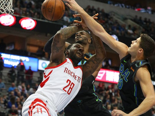 Houston Rockets forward Tarik Black (28) gets fouled by Dallas Mavericks forward Doug McDermott (20) as he goes up for a shot in the first half of an NBA basketball game Sunday, March 11, 2018 in Dallas. (AP Photo/ Richard W. Rodriguez)