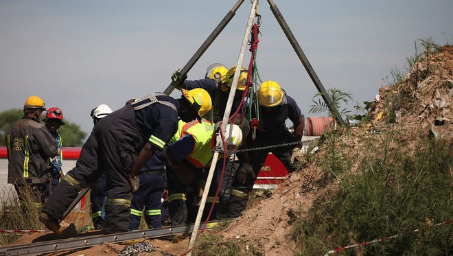 Emergency rescue workers attempt to free trapped illegal miners at a gold mine shaft near Benoni, South Africa, on Feb. 16.