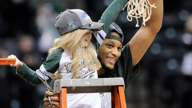 Michigan State forward Adriean Payne celebrates the Spartans' win against Michigan in the Big Ten Tournament along with Lacey Holsworth, age 8, as they hold one of the nets.