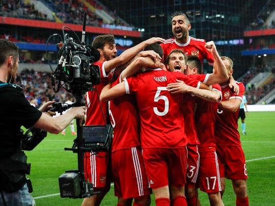 In this photo taken on Friday, June 9, 2017, A TV cameraman films while Russia's team players celebrate after scoring the goal during the international friendly soccer match between Russia and Chile at the VEB Arena stadium in Moscow, Russia. FIFA said Sunday it has reached a TV rights deal with Russian broadcasters for the Confederations Cup just six days before the tournament kicks off. (AP Photo/Alexander Zemlianichenko)