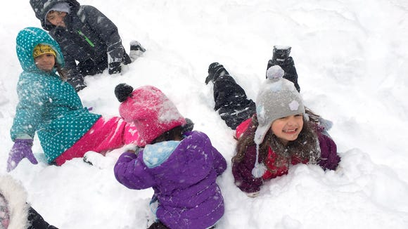 Chloe Cypher (right), 6, plays in the snow next to
