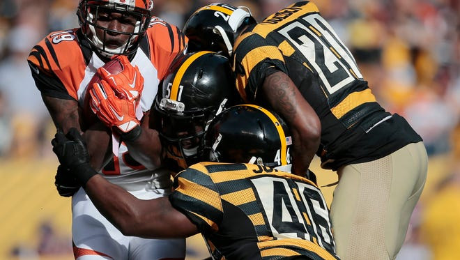 Cincinnati Bengals wide receiver Brandon Tate (19) is wrapped up on a reception in the second quarter of the NFL Week 8 game between the Pittsburgh Steelers and the Cincinnati Bengals at Heinz Field in Pittsburgh on Sunday, Nov. 1, 2015. At the half, the Steelers led the Bengals 7-6.