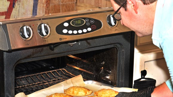 Korey Champagne, owner of Acadian Slice, removes his apple and bacon hand pies from the oven.
