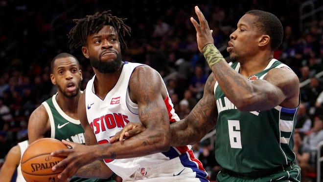 Pistons forward Reggie Bullock is defended by Bucks guard Eric Bledsoe.