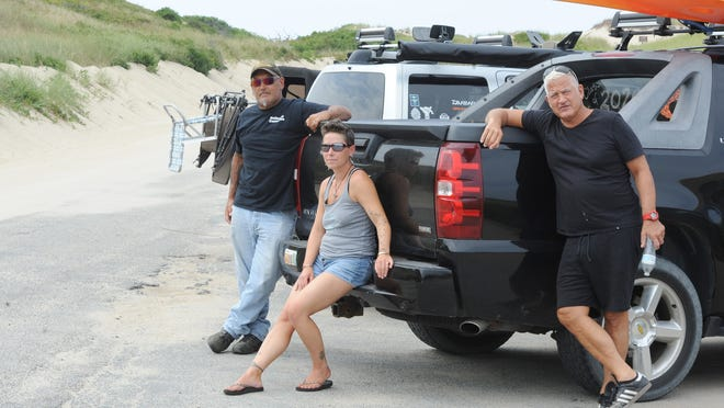 Peter and Victoria Attanasio, from left, of Truro, and Peter Kamerman, of Provincetown, are shown at the air station at the oversand vehicles entrance off Race Point Road in Provincetown. They want more information from Cape Cod National Seashore officials to justify restrictions on access to beach corridors. Victoria Attanasio has asked for data on four years of nesting shorebird activity.