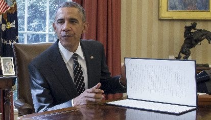 President Barack Obama finishes signing an executive order directing the federal government to reduce greenhouse gas emissions on March 19, 2015.