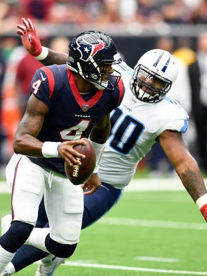 Texans quarterback Deshaun Watson (4) races away from Titans defensive end DaQuan Jones (90) in the first quarter at NRG Stadium on Sunday, Oct. 1, 2017.