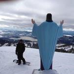 A snowboarder admires the Jesus statue at Whitefish Mountain ski resort in early February 2013 with Whitefish Lake in the background.