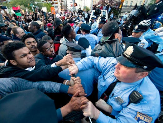 Protesters rush a police line after a rallyat City