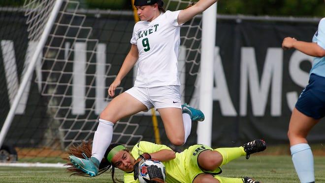 Olivet's Elizabeth Williams (9) leaps over Lansing Catholic goalkeeper Larisa Herdus after Herdus stopped Williams' shot, Thursday, May 31, 2018, in Williamston, Mich. Olivet won 1-0.