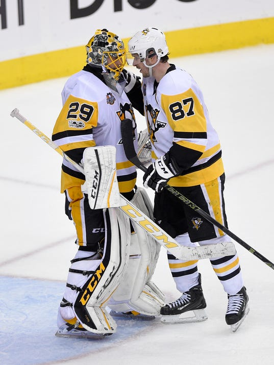 Pittsburgh Penguins goalie Marc-Andre Fleury (29) celebrates a win with center Sidney Crosby (87) after Game 2 in an NHL hockey Stanley Cup second-round playoff series against the Washington Capitals, Saturday, April 29, 2017, in Washington. (AP Photo/Nick Wass)