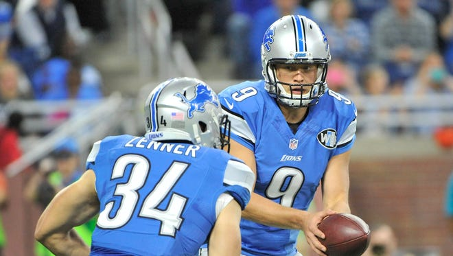 Lions quarterback Matthew Stafford hands off to running back Zach Zenner in the first quarter Sunday.