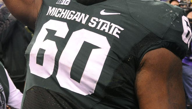 MSU's  Micajah Reynolds celebrates with the rest of the Spartans after beating Ohio State, 34-24, at the Big Ten Championship football game Saturday, 12/7/2013. MSU will be heading to the Rose Bowl.