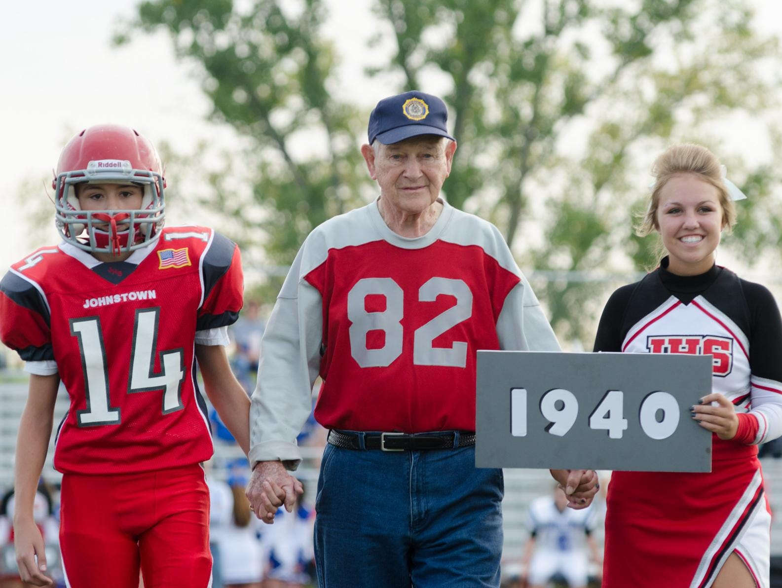 Don Jakeway, center, walks across the Johnstown field Friday on Alumni Night with his grandson, freshman Trenton Jakeway, 14, and a Johnstown cheerleader. It was the 75th anniversary of the 1940 team, which Jakeway played on.