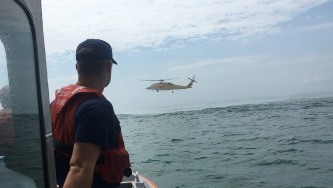 Coast Guard Petty Officer 3rd Class Ryan Brown, an engineer at Station Wachapreague, Virginia, gazes at an MH-60 Jayhawk helicopter flying over Metompkin Inlet August 2, 2016. The Jayhawk helicopter crew from Air Station Elizabeth City, North Carolina, assisted the boat crew in rescuing two people from a 15-foot boat taking on water. (U.S. Coast Guard photo by Coast Guard Petty Officer 2nd Class Ryan Sanchez/Released)