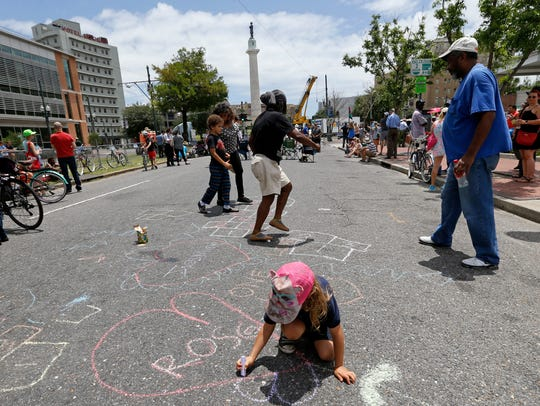 Roscoe Adair, 6, draws a heart with chalk in the street