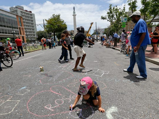 Roscoe Adair, 6, draws a heart with chalk in the street as workers prepare to take down the statue of former Confederate general Robert E. Lee in New Orleans on May 19, 2017.