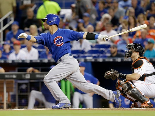 Chicago Cubs' Willson Contreras, left, follows through on his two-run home run against the Miami Marlins in the first inning of a baseball game, Friday, June 24, 2016, in Miami. Ben Zobrist also scored on the home run. (AP Photo/Alan Diaz)