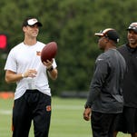 Robert Livingston, Bengals defensive quality control/special teams assistant, left, talks with Vance Joseph, position coach for defensive backs, and Mark Carrier, defensive back coach, right, during Tuesday's OTAs.