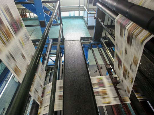 The paper rolls through the press. The presses run