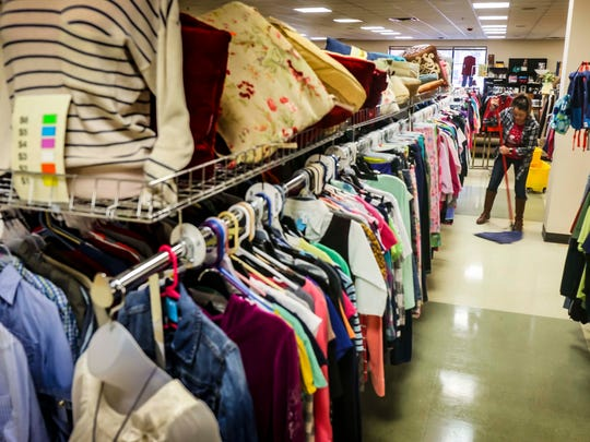 Store manager Irma Donan mops the floors between the clothes racks at theRenew Resale Shop Tuesday, April 3, 2018, in the Park Fair Mall in Des Moines, Iowa.