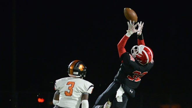 Delsea's Khaliel Burnett makes a catch with  Woodrow Wilson's Hydir Moore defending during Friday night's football game. 10.27.17.
