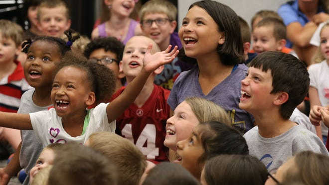 """Children react during an experiment at the Mad Science assembly """"Fizz, Boom, Read!"""" at Johnston Public Library on June 4. This was the library's first big program to help kick off its summer reading program."""