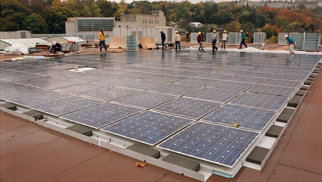 Workers place solar tiles.