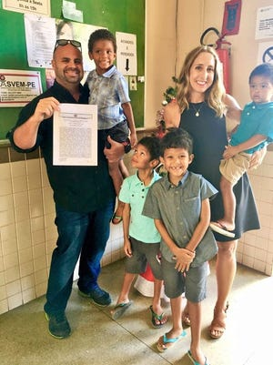 At the courthouse lobby in Paulista, Brazil, Brandon Pratt of North Liberty proudly displays the final adoption decree creating this large, happy new family. He holds Enzo while his wife Jennifer holds William. Cristiano stands at left and Leandro at right.