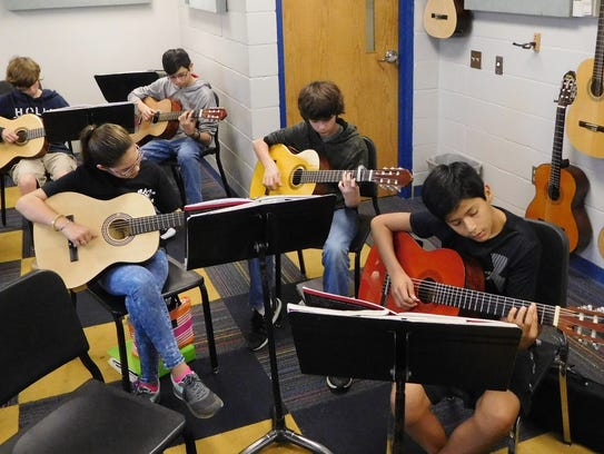 Students refine their guitar skills at Raa Middle School.