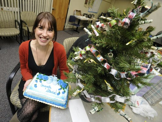 Stacia Fleegal poses with her cake and a money tree. The entire newsroom contributed to the tree.