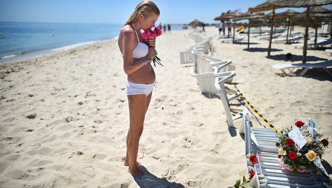 A woman grieves as she lays flowers at the beach next to the Imperial Marhaba hotel on June 27, 2015 in Souuse, Tunisia.