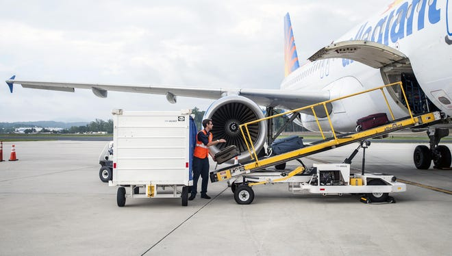 Dan Taha, supervisor with World Wide Flight Services, loads bags onto a ramp for an Allegiant Air flight from Asheville Regional Airport.