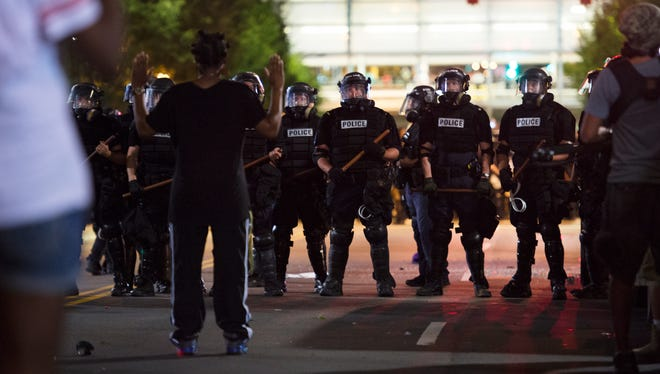 Police in riot gear stand in front of protestors by the Omni Hotel in Charlotte.