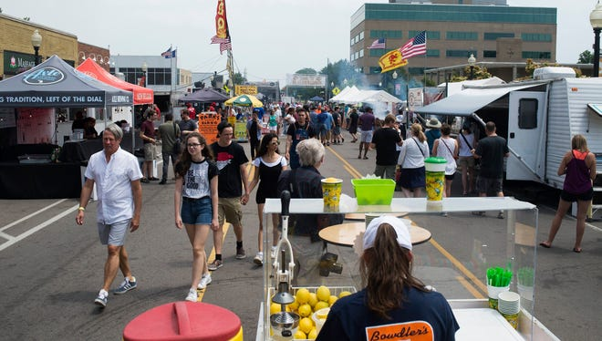 People walk among food vendors during the Brews, BBQ, Bourbon Festival on Saturday, June 17, 2017 in downtown Ferndale. The three-day festival features live music entertainment as well as a variety of food and drink options.