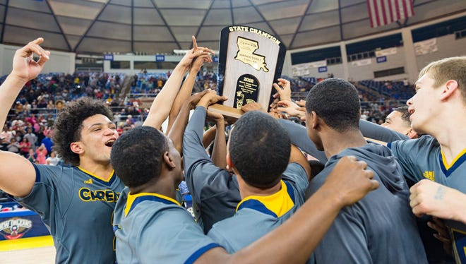 The Carencro High basketball team celebrates its win over Woodlawn for the Class 4A state basketball championship Friday March 9, 2018.