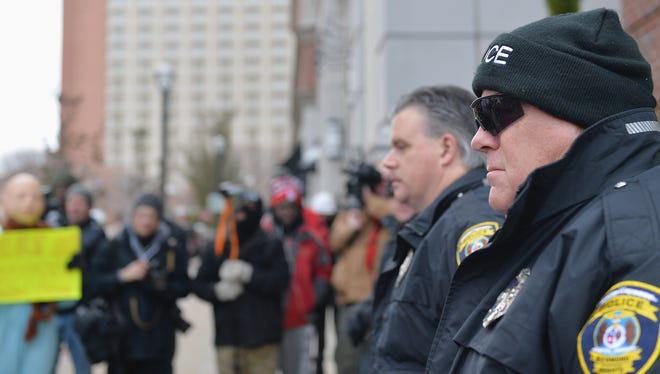 Clayton police officers keep a watchful eye during a peaceful protest  in Clayton, Mo. The governor of Missouri declared a state of emergency and activated the National Guard ahead of a grand jury decision in the case of a black teenager shot and killed by a white police officer.