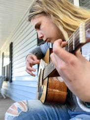 "Kaylee Muthart, who is blind, plays the guitar on her front porch. She is trying to learn the chords to Green Day's ""Time of Your Life."""