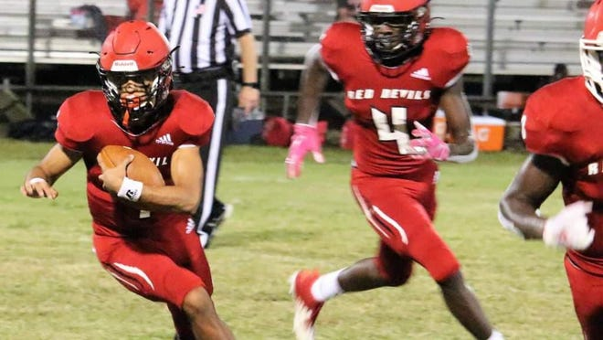 Red Devil quarterback Brayden Frazier carries the ball with blocking help from Jamian Risher.