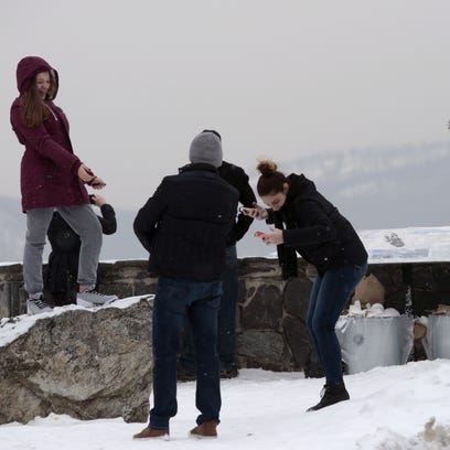 A family takes pictures at the scenic overlook at Route