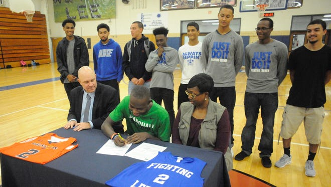 Lee High's Darius George signs his national letter of intent to play basketball at Marshall University. His high school teammates watched, as did Lee  coach, Jarrett Hatcher, left, and his mother, Maria Hill.