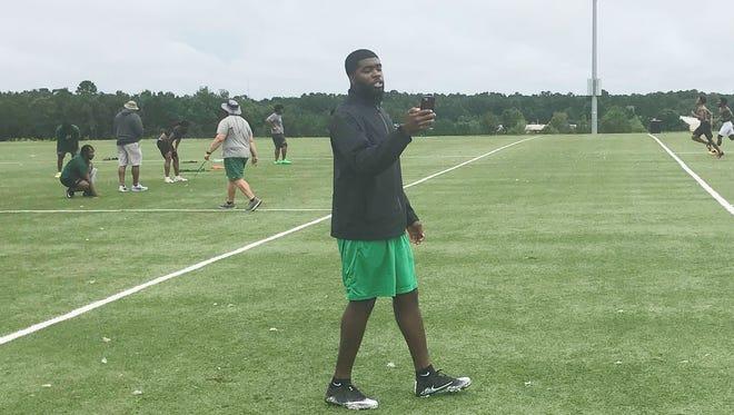 Jelani Berassa clocks players running timed drills during practice.