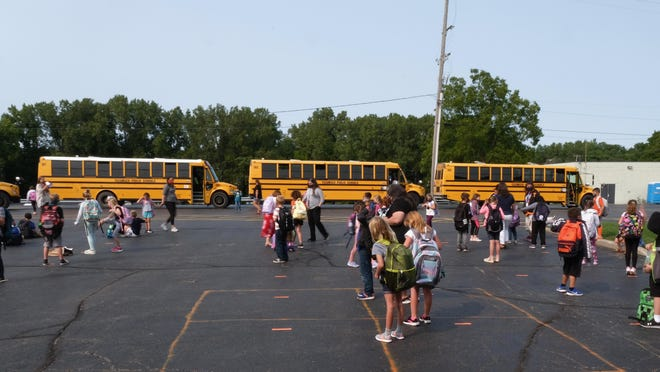 Students prepare to board buses at Tecumseh Compass Learning Center in Tecumseh on Tuesday.