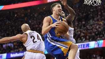 Golden State Warriors guard Klay Thompson (11) shoots the ball past Cleveland Cavaliers forward Richard Jefferson (24) and center Tristan Thompson (13) during the second quarter in game three of the NBA Finals at Quicken Loans Arena.